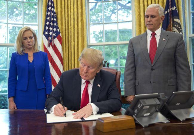 川普总统在白宫椭圆形办公室的坚毅桌上签署行政令,彭斯副总统站在他的左边,国土安全部长尼尔森站在他的右边。(2018年6月20日)