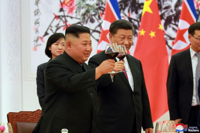 2018年6月19日,中国国家主席习近平和朝鲜领导人金正恩在欢迎宴会上举杯祝福。