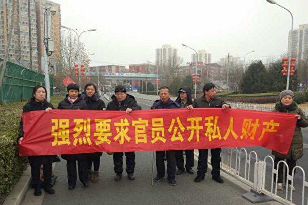 """新年长假最后一天,在京上访的访民在北京南站,拉起写有""""强烈要求官员公开私人财产""""的横幅。(维权网)"""