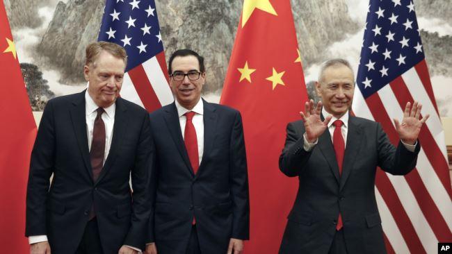 美国财政部长姆努钦(中)与贸易代表莱特希泽(左)在北京会晤前,中国副总理刘鹤(右)与他交谈时的手势。(2019年5月1日)